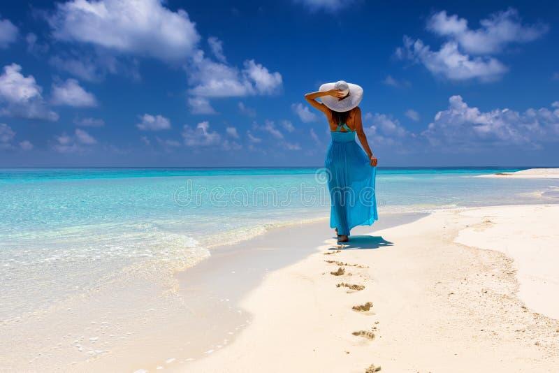 Frau in den blauen Kleiderwegen auf einem tropischen Strand lizenzfreie stockfotografie