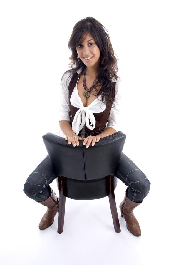 Frau in den casuals, die auf Stuhl sitzen lizenzfreies stockbild
