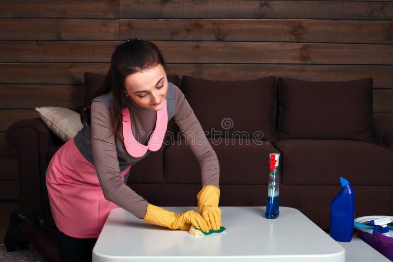 Frau in den einheitlichen und Gummihandschuhen säubert Tabelle lizenzfreies stockfoto