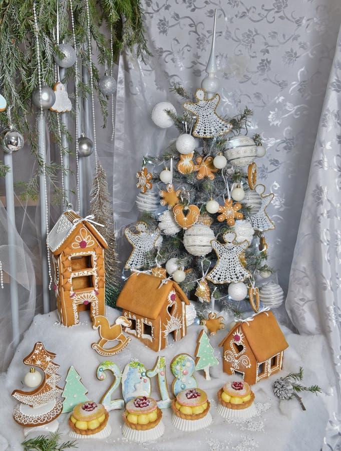 Frau in den Feiertagsvorbereitungen, welche die Verglasung auf Lebkuchenhaus Weihnachtsbäume setzen lizenzfreies stockbild