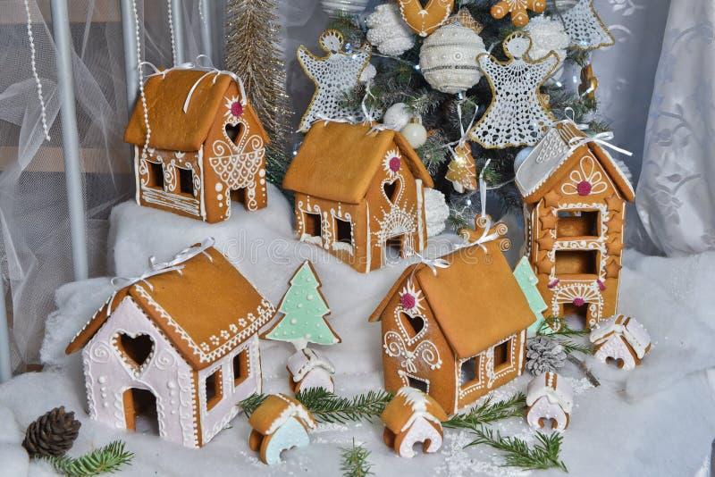 Frau in den Feiertagsvorbereitungen, welche die Verglasung auf Lebkuchenhaus Weihnachtsbäume setzen lizenzfreie stockbilder