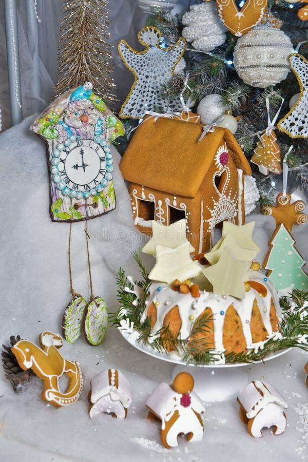 Frau in den Feiertagsvorbereitungen, welche die Verglasung auf Lebkuchenhaus Weihnachtsbäume setzen lizenzfreie stockfotografie