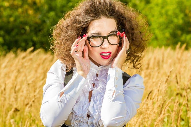 Frau in den Gläsern, die auf Natur aufwerfen stockfotografie