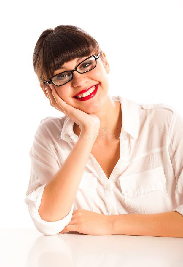 Frau in den Gläsern und in roten Lippen, lächelnd am Schreibtisch lizenzfreie stockfotografie