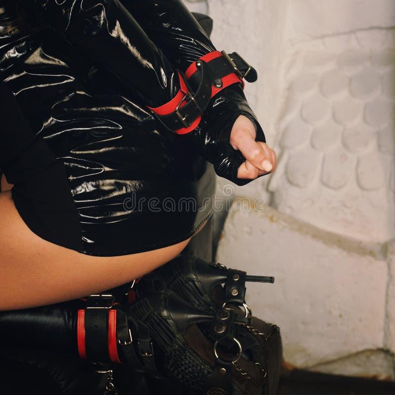 Frau in den Handschellen, sexy Frauenfigur kleidete in BDSM-Art an lizenzfreie stockfotografie