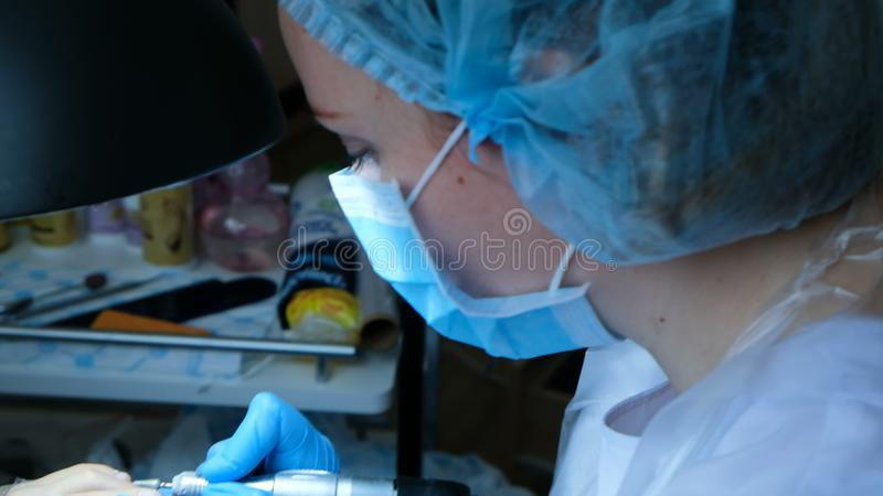 Frau in den Handschuhen tut Pediküre und behandelt Zehennagelhäutchen stockfotos