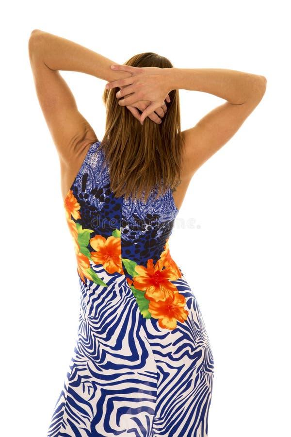 Frau in den hawaiin Kleiderhänden auf Haarrückseite lizenzfreies stockfoto