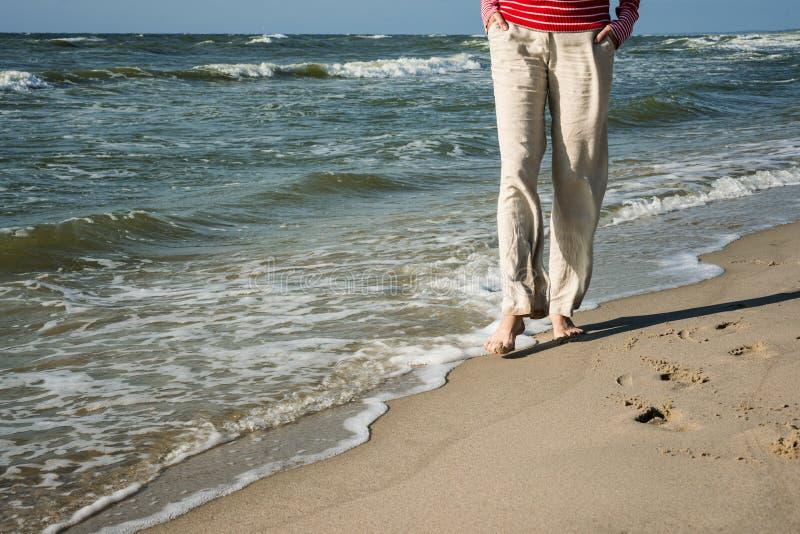 Frau in den Hosen geht durch das Meer lizenzfreie stockfotos