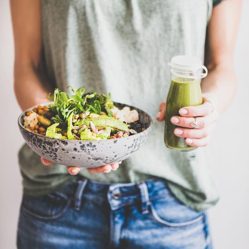 Frau in den Jeans, die gesundes superbowl und Smoothie, quadratische Ernte halten stockfotos