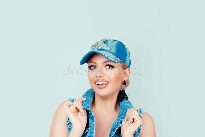 Frau in den Jeans Hut und Jacke, die das lächelnde Lachen des Kragens hält, Sie betrachtend lizenzfreie stockfotos
