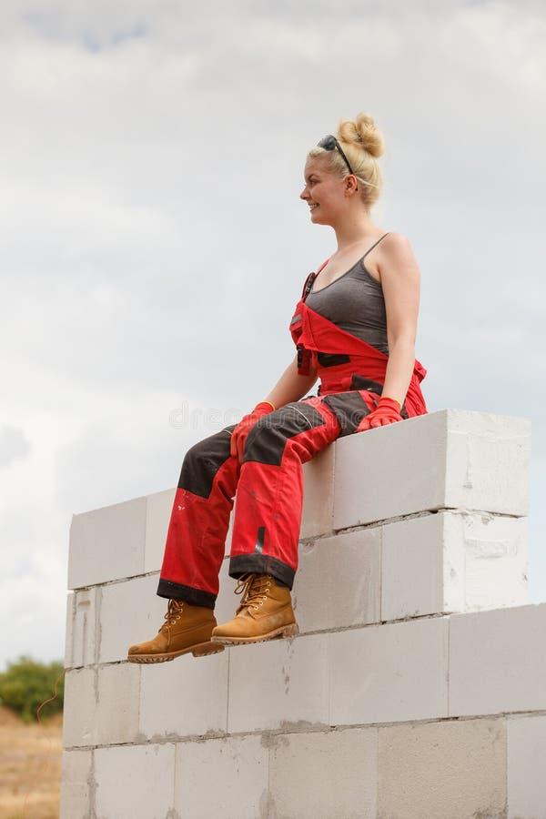 Frau in den Jeansstoffen, die Pause auf Baustelle machen lizenzfreie stockbilder