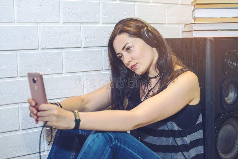 Frau in den Kopfhörern hörend auf ein audiobook an einem Telefon, das auf Wandhintergrund sitzt lizenzfreie stockfotos