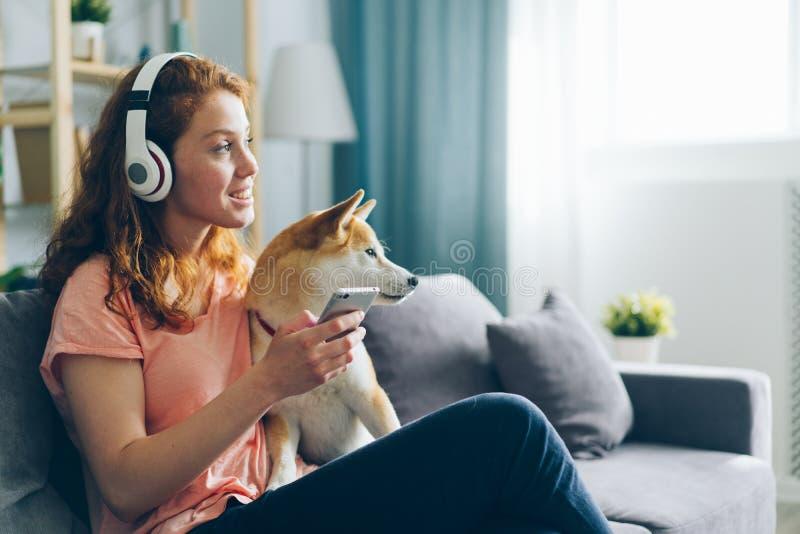 Frau in den Kopfhörern hörend auf Musikliebkosungshund auf Couchholding Smartphone stockfotos