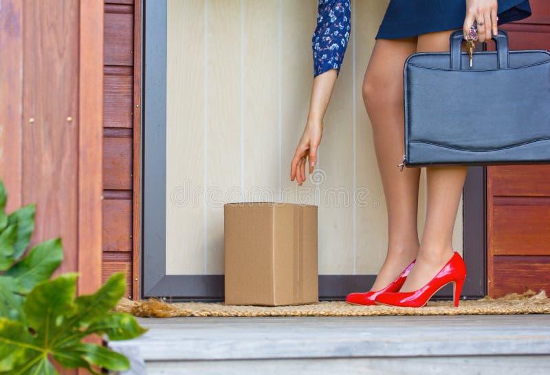 Frau in den roten Fersen sammelt Paket an der Haustür des Hauses lizenzfreie stockfotos