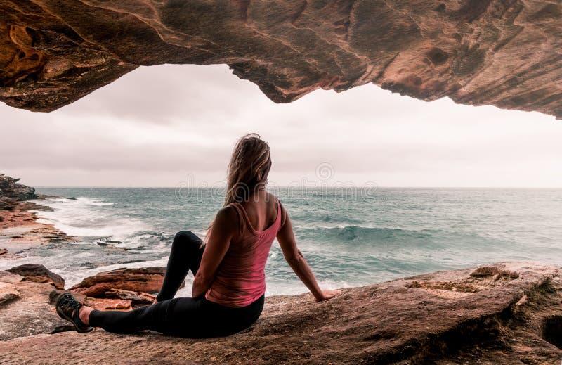 Frau in der aktiven Abnutzung, die durch den Ozean sitzt lizenzfreie stockfotos