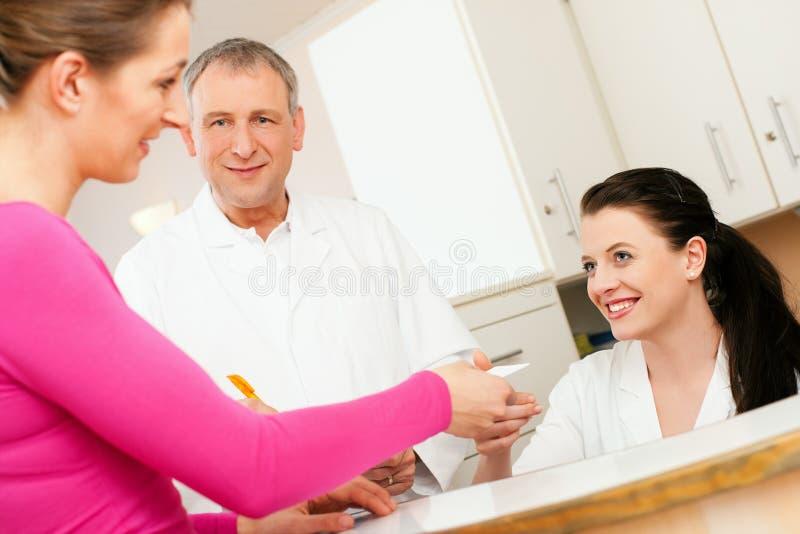 Frau an der Aufnahme der Klinik stockbild