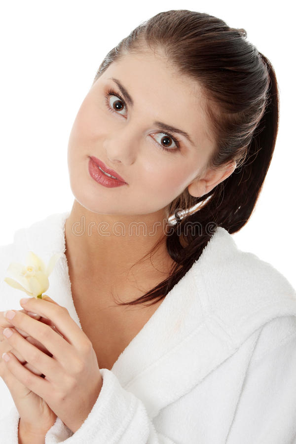 Frau in der Bademantelholding-Orchideeblume lizenzfreie stockbilder