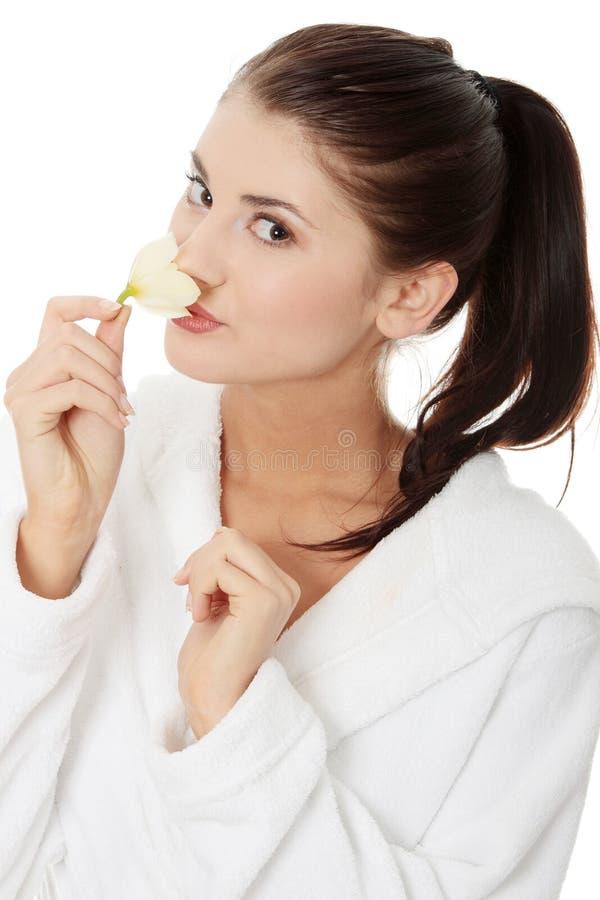 Frau in der Bademantelholding-Orchideeblume stockfoto
