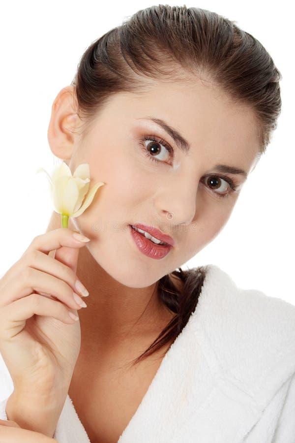 Frau in der Bademantelholding-Orchideeblume stockfotos