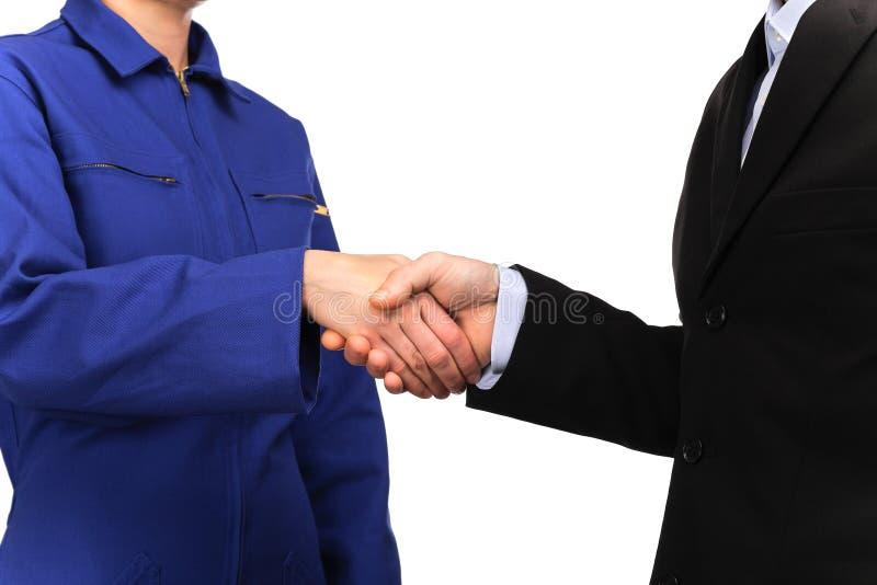 Frau in der blauen Arbeitsuniform und in einem Mann kleidete in der Klage an, die Hände rüttelt stockfotografie