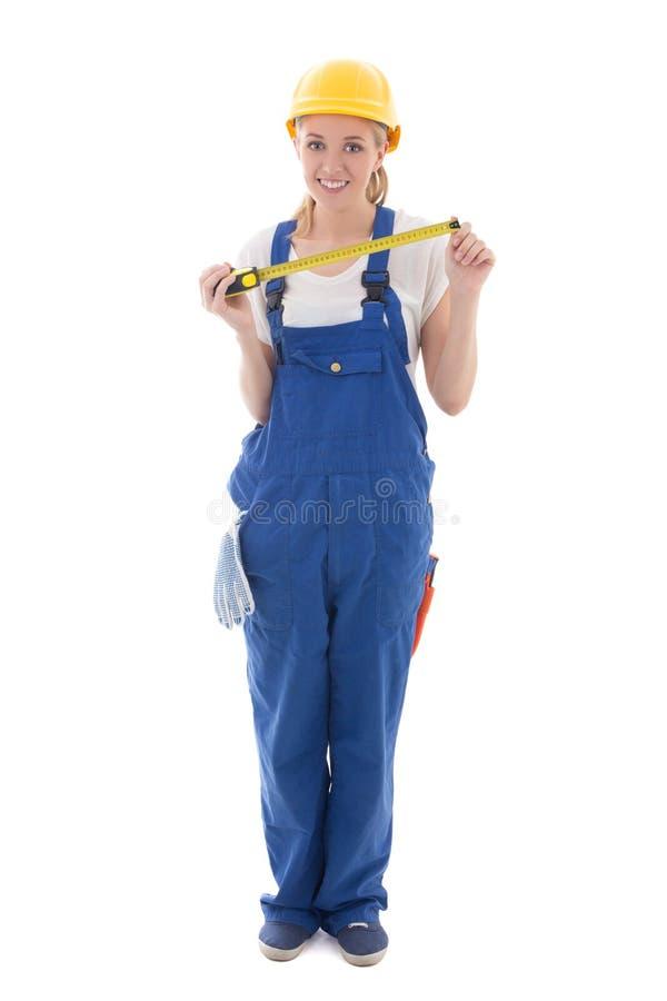 Frau in der blauen Erbaueruniform und -sturzhelm, die Maßband hält, ist lizenzfreie stockfotografie