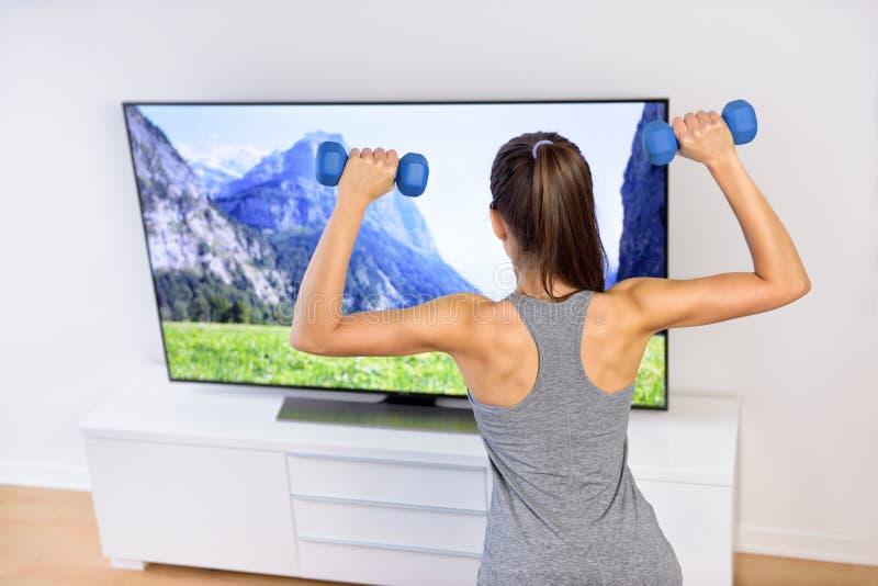 Frau der Eignung zu Hause -, die vor Fernsehen ausarbeitet stockfotografie