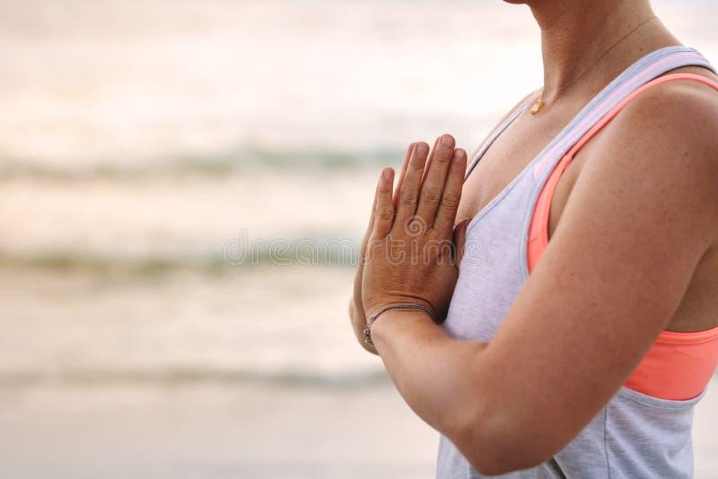 Frau in der Eignungsabnutzung, die Yoga am Strand tut lizenzfreie stockfotos