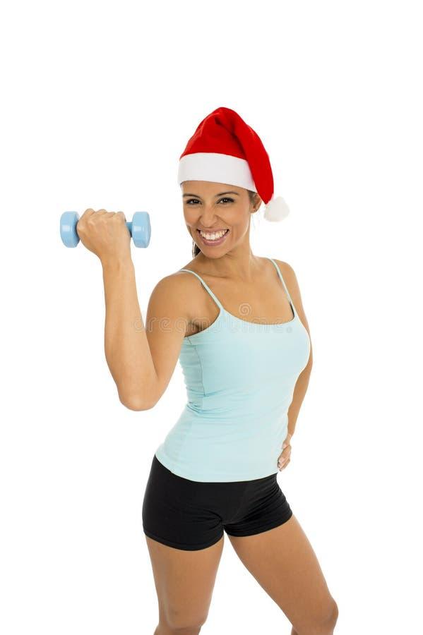 Frau in der Eignungskleidung und in Weihnachtsmann-Weihnachtshut, die Gewichtsdummköpfe halten stockfotografie