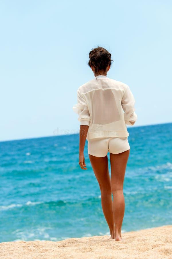 Frau in der eleganten weißen Ausstattung gehend in Richtung zum Wasser. lizenzfreie stockbilder