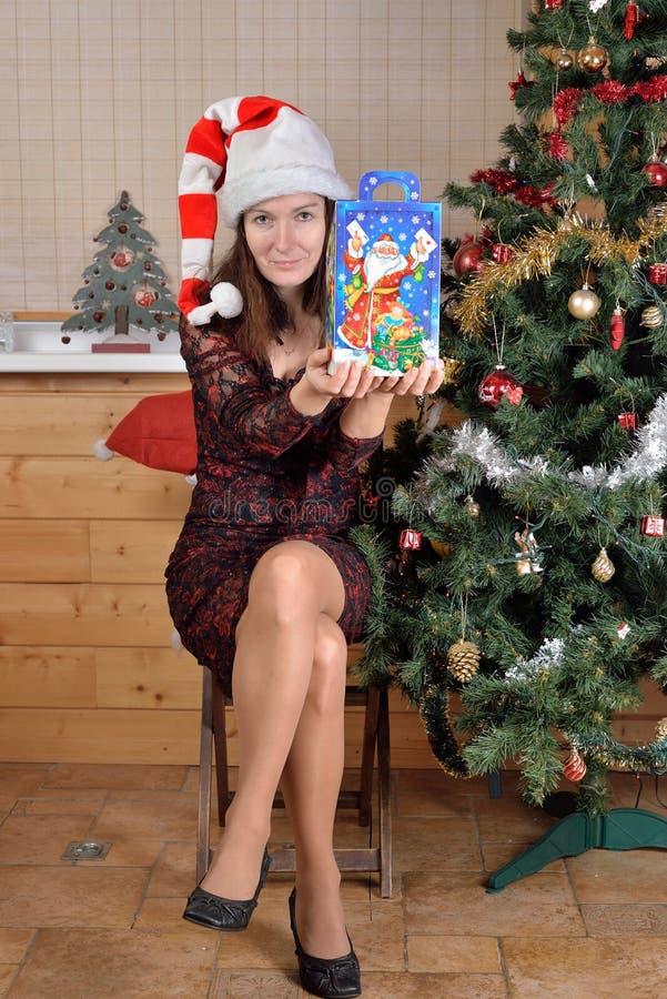 Frau in der festlichen Kappe bietet ein Geschenk am Weihnachtsbaum an stockfotos
