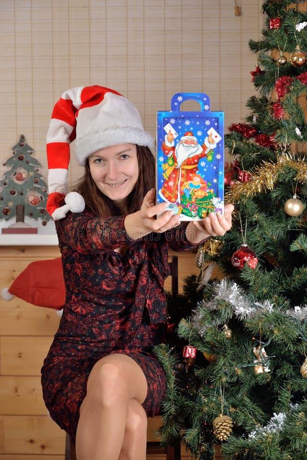 Frau in der festlichen Kappe bietet ein Geschenk am Weihnachtsbaum an lizenzfreies stockfoto