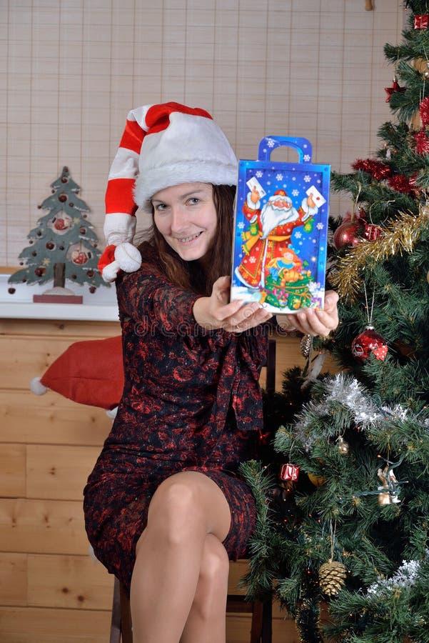 Frau in der festlichen Kappe bietet ein Geschenk am Weihnachtsbaum an stockfotografie