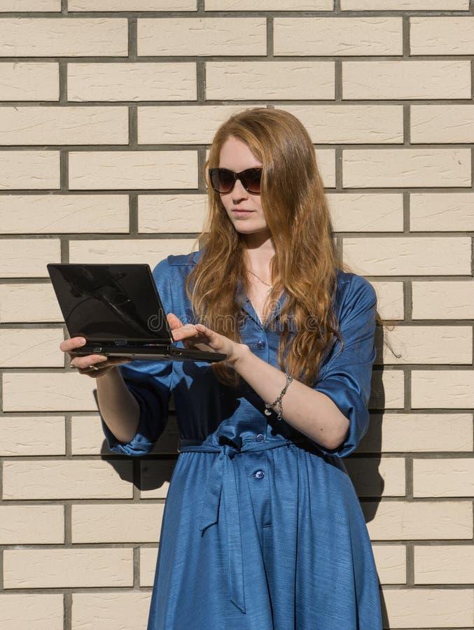 Frau in der Freizeitkleidung lehnt sich an der weißen Backsteinmauer Rotes Haarmädchen ist außerhalb eines Büros, Holding eine Ta stockbild
