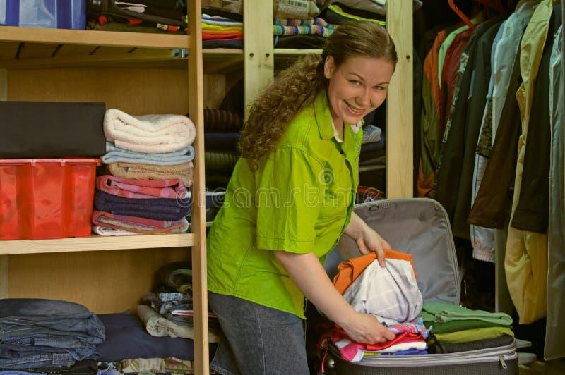 Frau in der Garderobe packt Sachen in einen Koffer lizenzfreie stockbilder