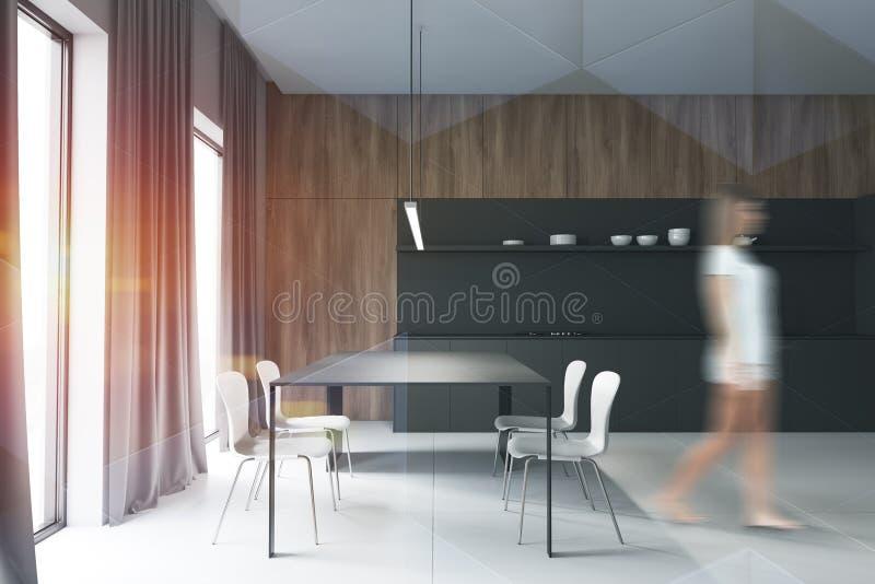Frau in der grauen und hölzernen Küche, Vorhänge stockbild