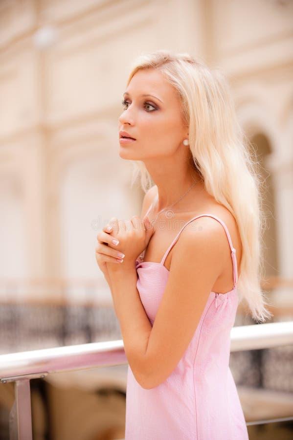 Frau in der großen Halle am Geländer lizenzfreie stockfotografie