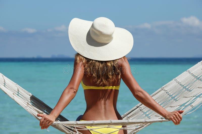 Frau in der Hängematte auf Strand lizenzfreie stockbilder