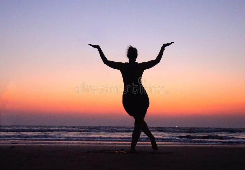 Frau in der Haltung, die Shiva in Sonnenuntergangrosa Himmel nahe Meer in Indien tanzt Tanz ist nützlich! Symbol von Indien lizenzfreie stockbilder