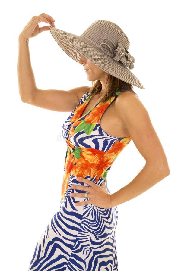 Frau in der hawaiin Kleiderhand auf Hut lizenzfreies stockbild