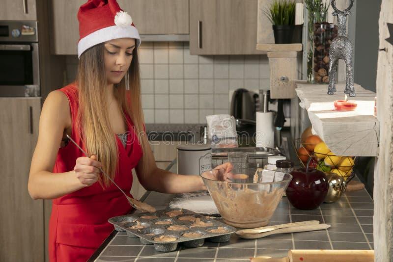 Frau in der Küche bereitet kleine Kuchen für ein Glättungsweihnachtsfest zu stockbild