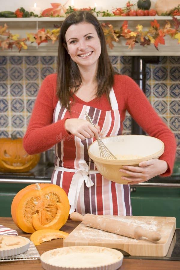 Frau in der Küche, die Halloween-Festlichkeiten bildet stockfotos