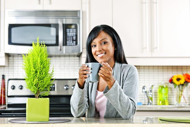 Frau in der Küche mit Kaffeetasse lizenzfreie stockfotos