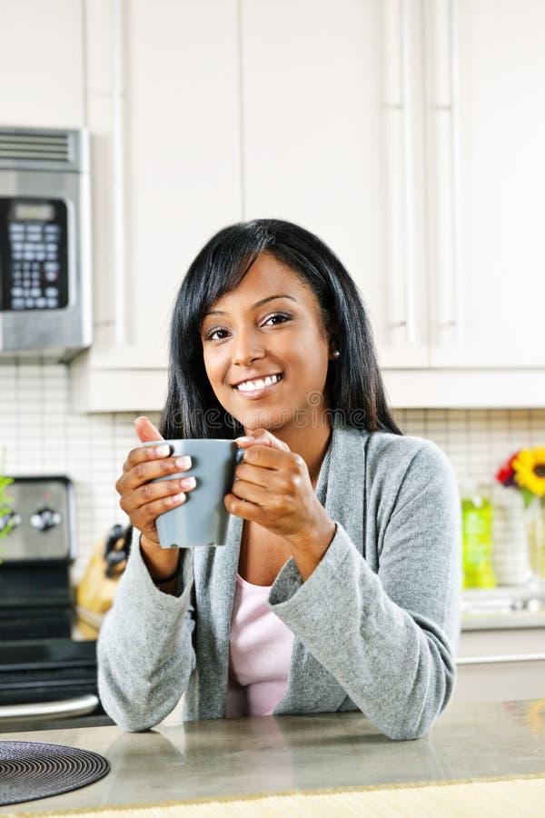 Frau in der Küche mit Kaffeetasse stockbild