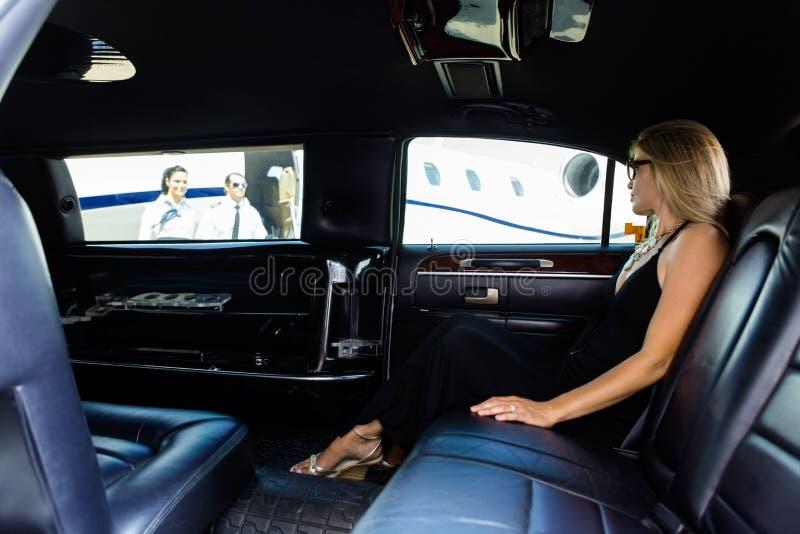 Frau in der Limousine am Flughafenabfertigungsgebäude lizenzfreie stockfotos