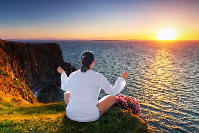 Frau an der Meditation auf Klippe stockfotografie