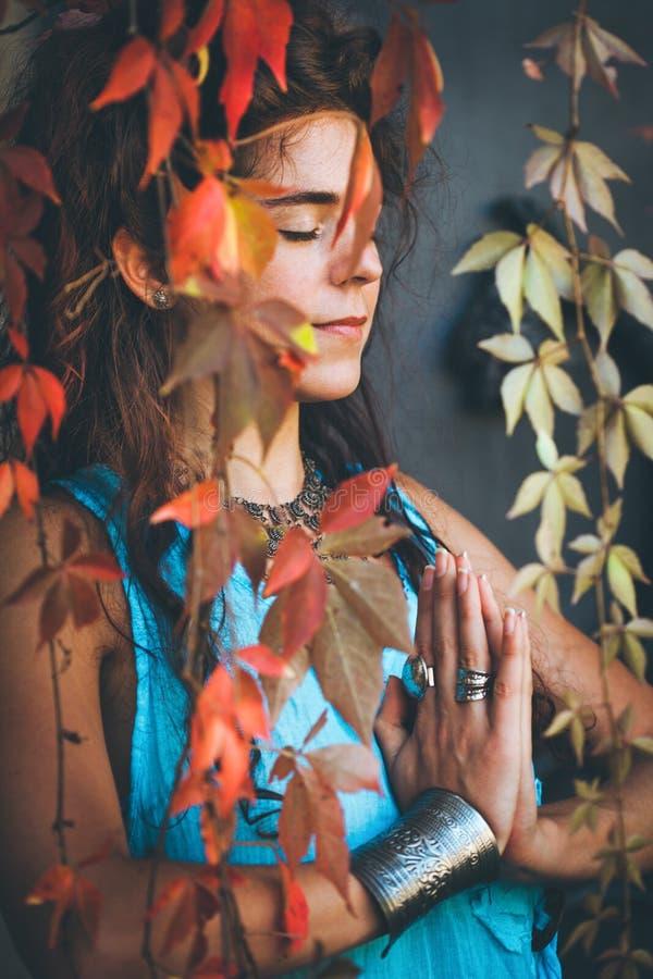 Frau in der Meditation hinter Blättern lizenzfreie stockbilder