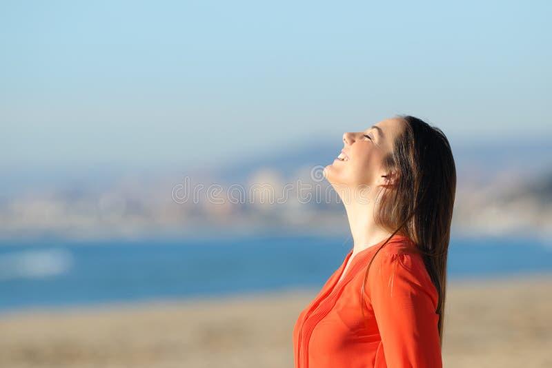 Frau in der orange atmenden Frischluft auf dem Strand stockfotografie