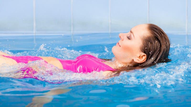 Frau in der rosa Badeanzugschwimmen im blauen Pool auf ihr zurück lizenzfreie stockfotos