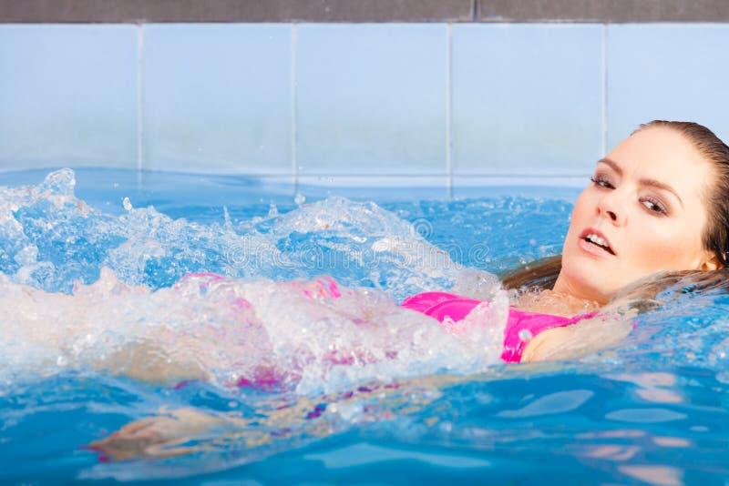 Frau in der rosa Badeanzugschwimmen im blauen Pool auf ihr zurück stockbild