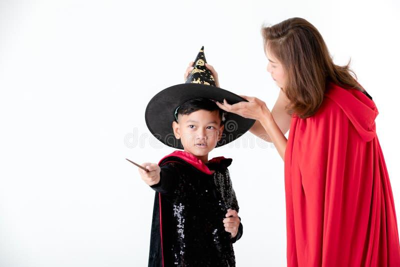 Frau in der roten Abdeckung mit der Haube, die Sorgfalt für Jungen in Kostüm dres anwendet lizenzfreie stockfotos